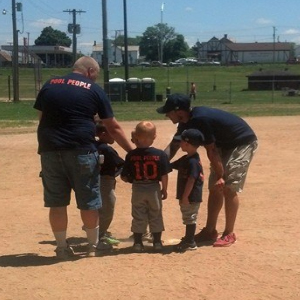 little league baseball player standing over home plate talking to two coaches