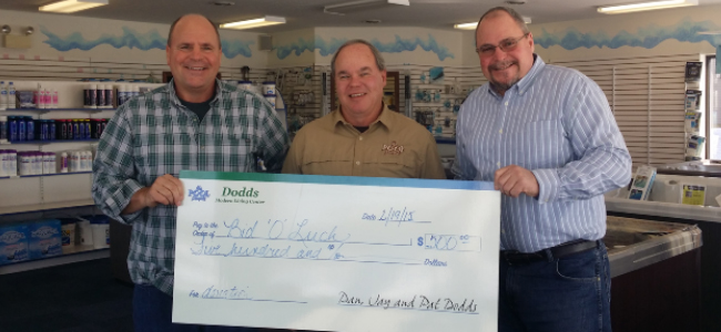 three men standing in showroom holding a donation check