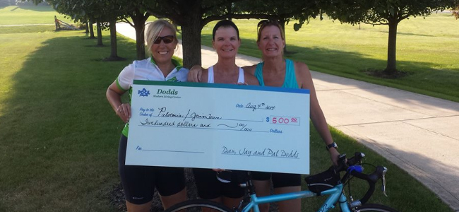 three ladies outside on bikes and holding a donation check